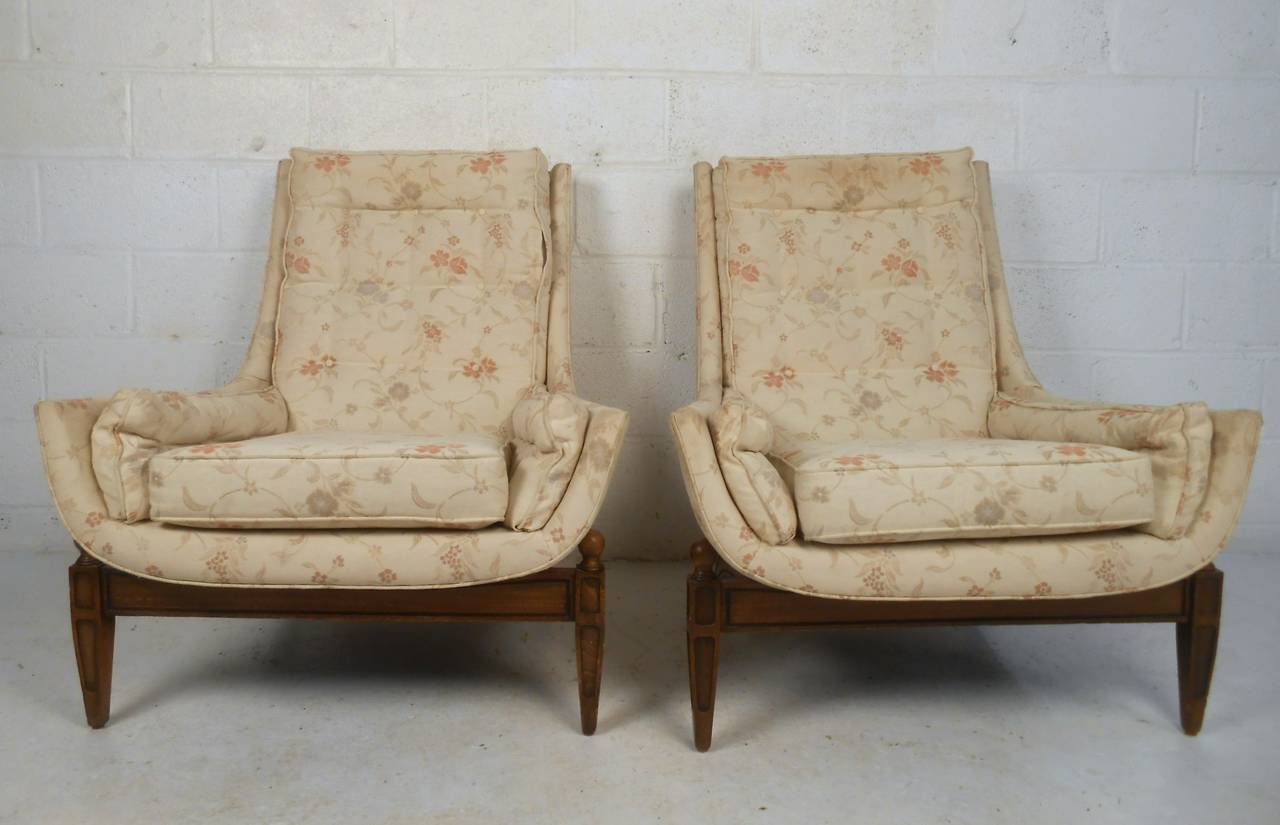 This matching pair of unique and comfortable lounge chairs feature unique sculpted bases, tapered legs, and stylish low profile armrests. Matching ottoman included, please confirm item location (NY or NJ).