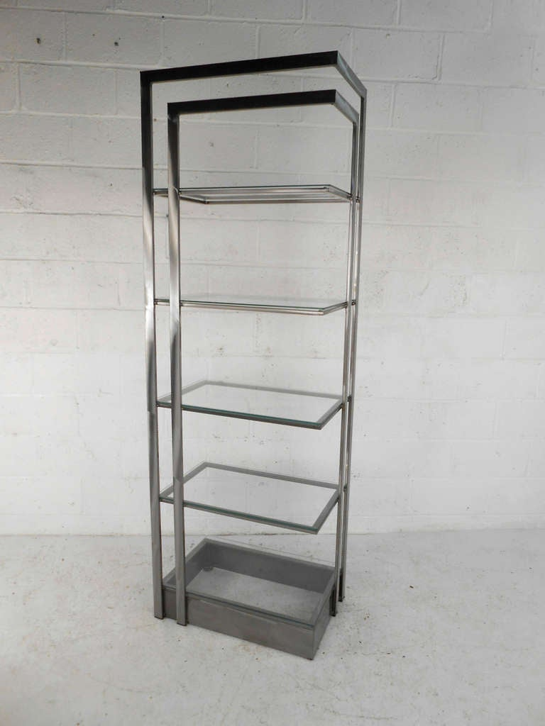 This Italian étagère features a solid construction of brushed stainless steel with five glass shelves for display. Striking modern bookshelf for home or shop storage and display. Please confirm item location (NY or NJ) with dealer.