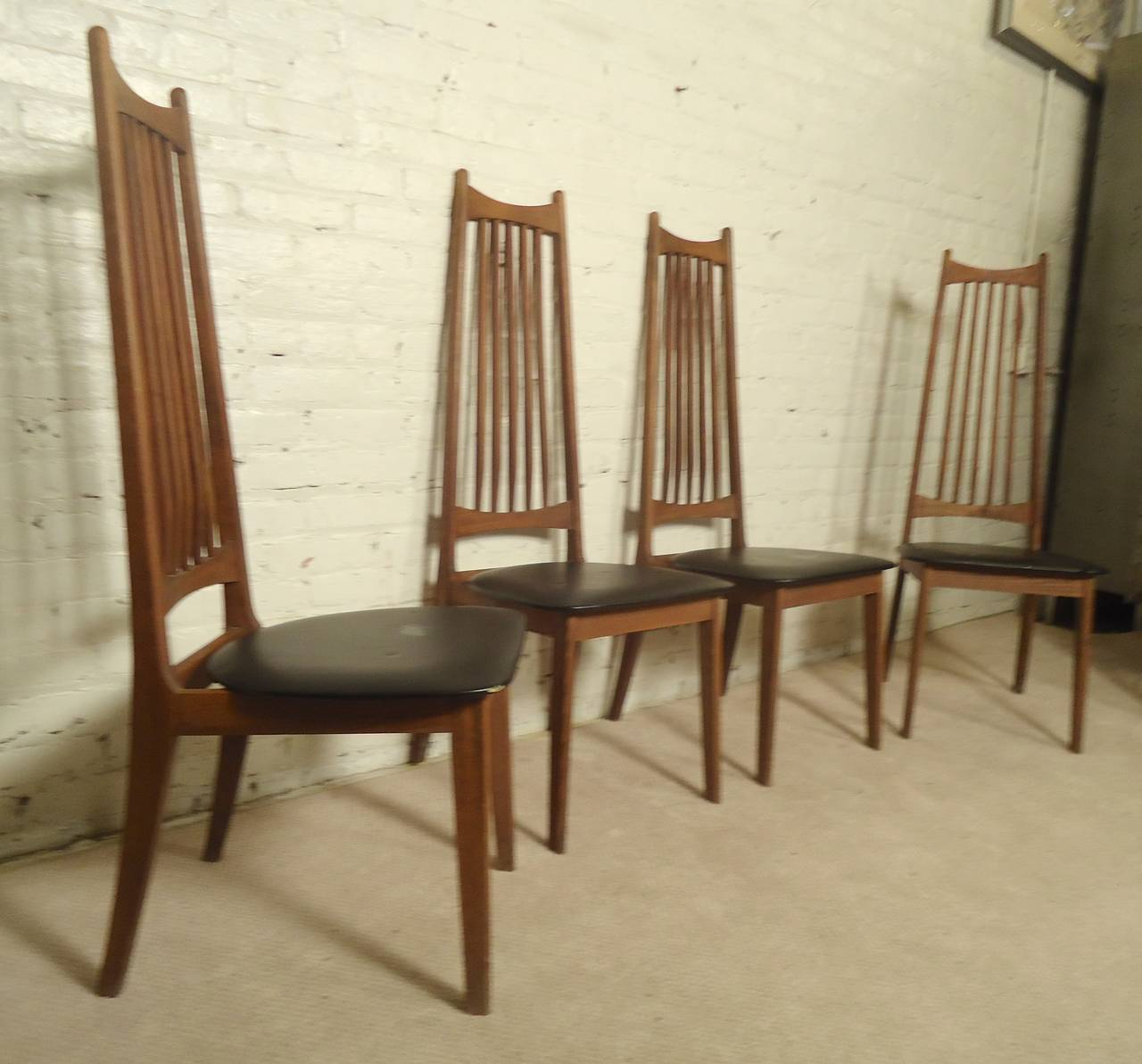 Vintage modern slat back chairs with exaggerated walnut frame. Sculpted slats, black vinyl seats.  (Please confirm item location - NY or NJ - with dealer)