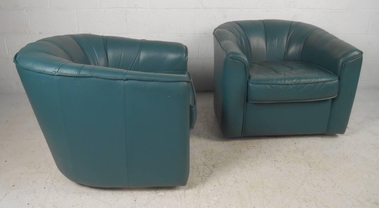 Pair of modern barrel back club chairs with swivel bases upholstered in soft leather. The elaborate dark green leather, overstuffed removable cushions, and ability to swivel ensures comfort and convenience. Stylish lounge chairs perfect for any