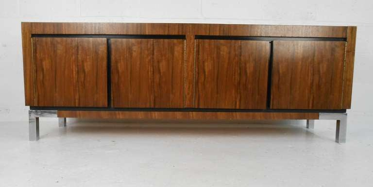 Dramatic rosewood pattern, Mid-Century four-door credenza with storage drawer. Please confirm item location (NY or NJ) with dealer.