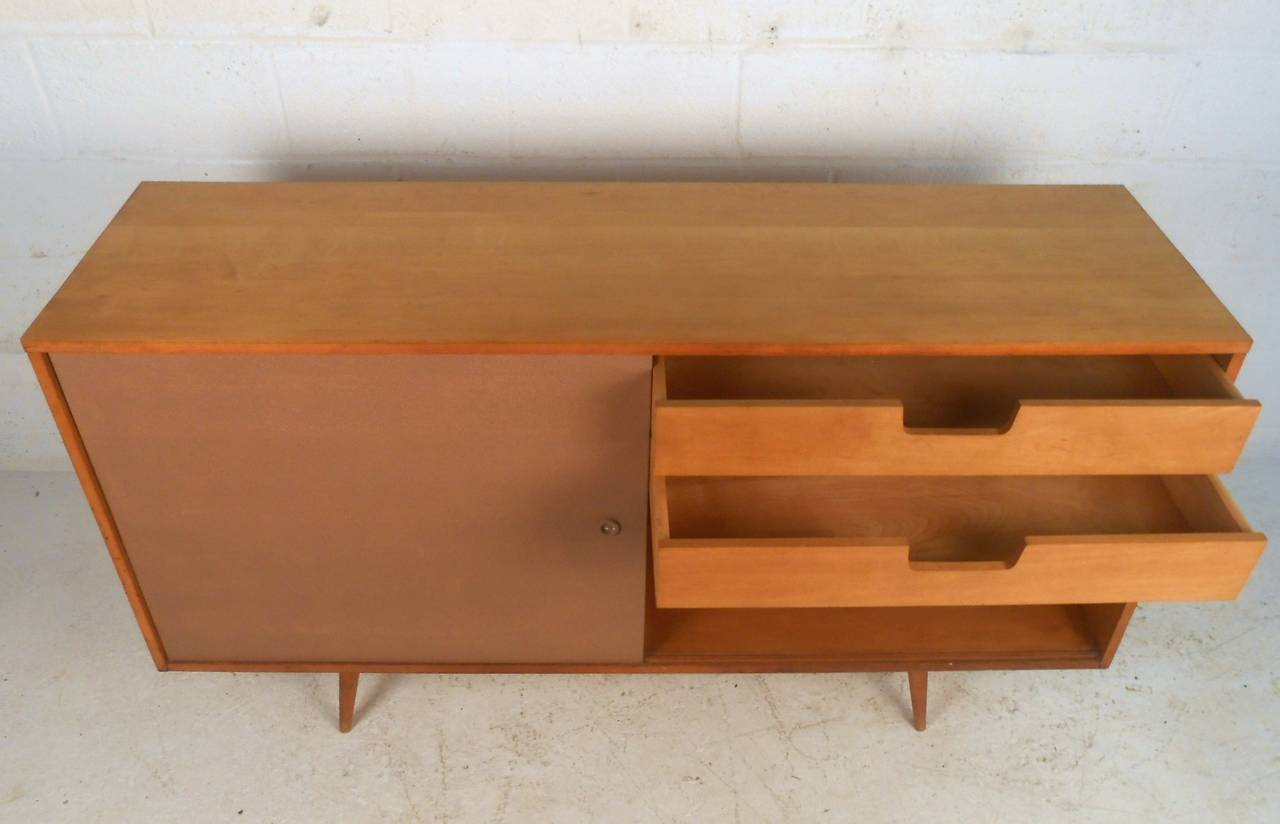 This gorgeous sideboard features sliding doors for easy access to spacious cabinet storage, and extra drawers for organization. Classic McCobb style and tapered legs add to it's vintage charm. Original manufacturer's tag, please confirm item