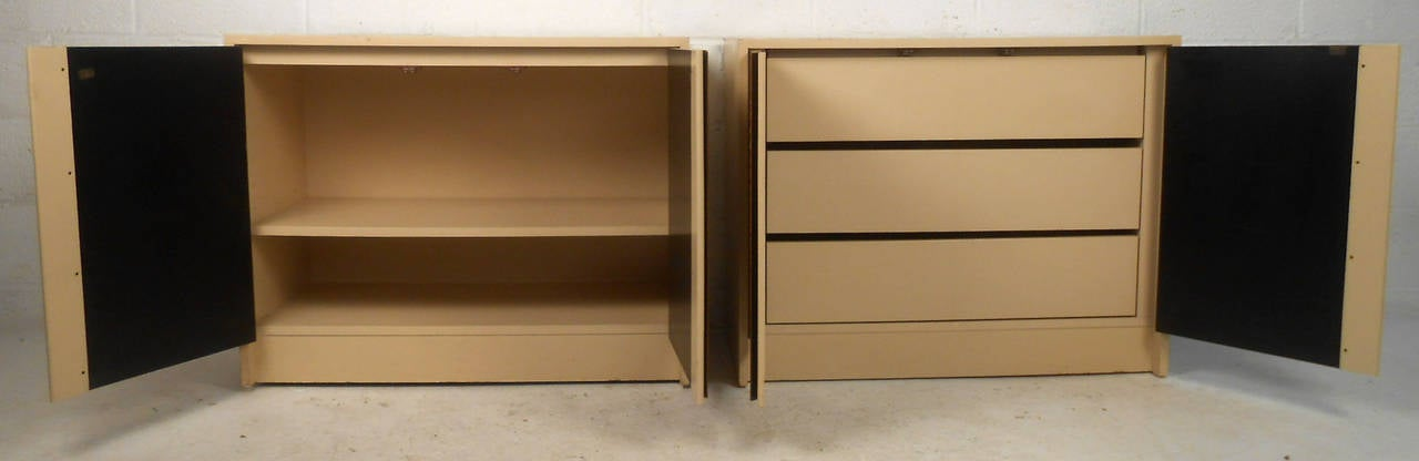 This stylish mid-century modern set of cream colored cabinets features rich burl-wood doors with chrome accents and spacious interior storage. Matching Milo-Baughman style cabinets offer both drawer and shelf storage respectively.   (Please confirm