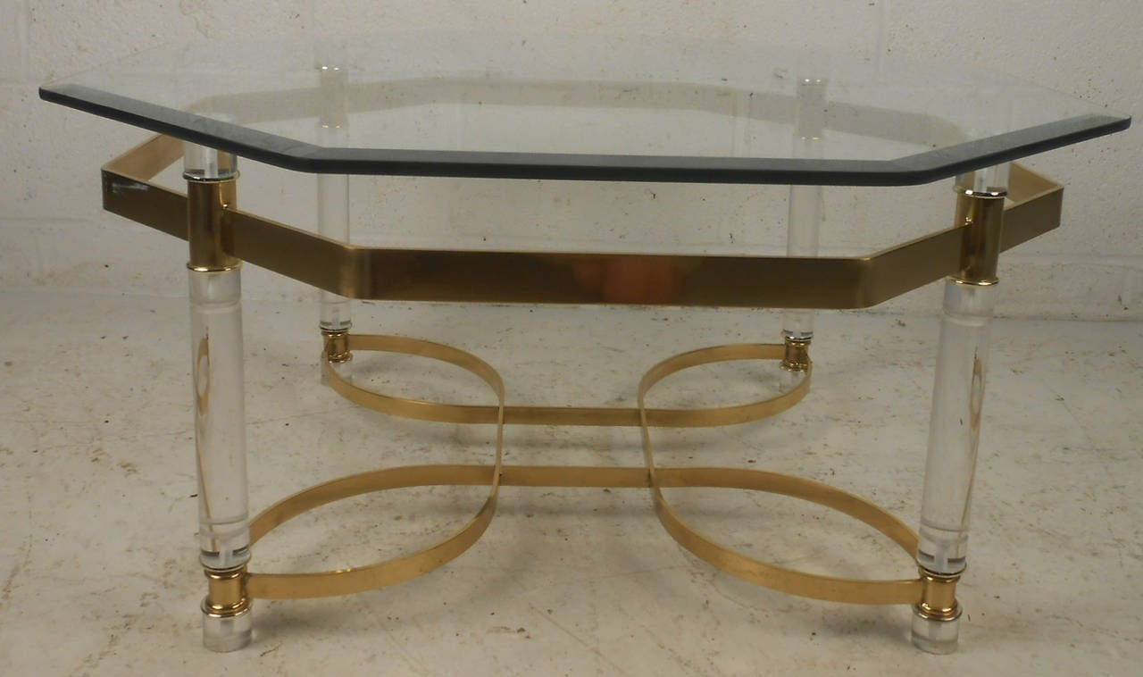 Vintage modern coffee table featuring beautifully sculpted brass base with Lucite trim, topped with a octagonal glass top. Designed in the manner of Charles Hollis Jones. Please confirm item location (NY or NJ).