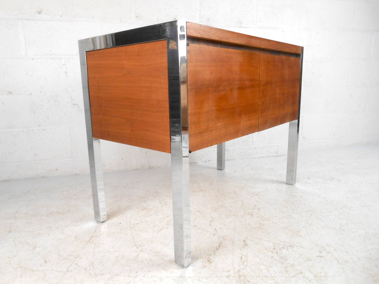 This midcentury cabinet features solid walnut construction, a chrome frame, and two door design with adjustable interior shelf which offers ample storage and a modern accent to any home or office space.  Please confirm item location (NY or NJ)