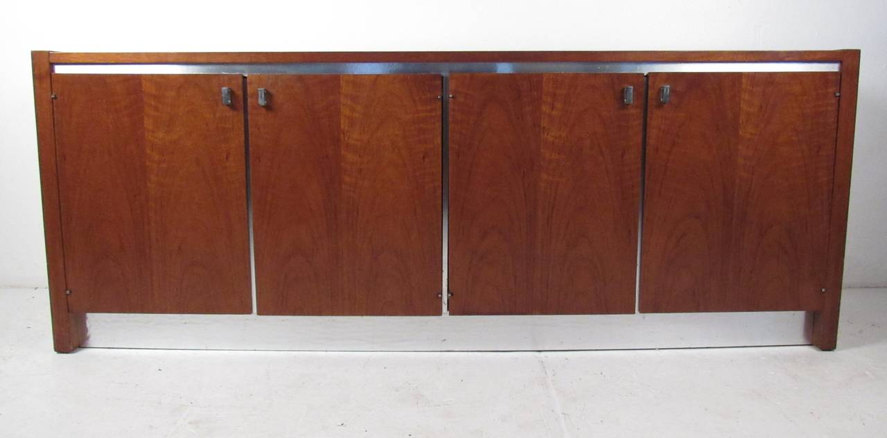 Mid-Century walnut credenza by Founders Furniture Co. Well-constructed cabinet features four doors with aluminium pulls and accent trim opening to reveal two adjustable shelves and four storage drawers. Please confirm item location (NY or NJ) with