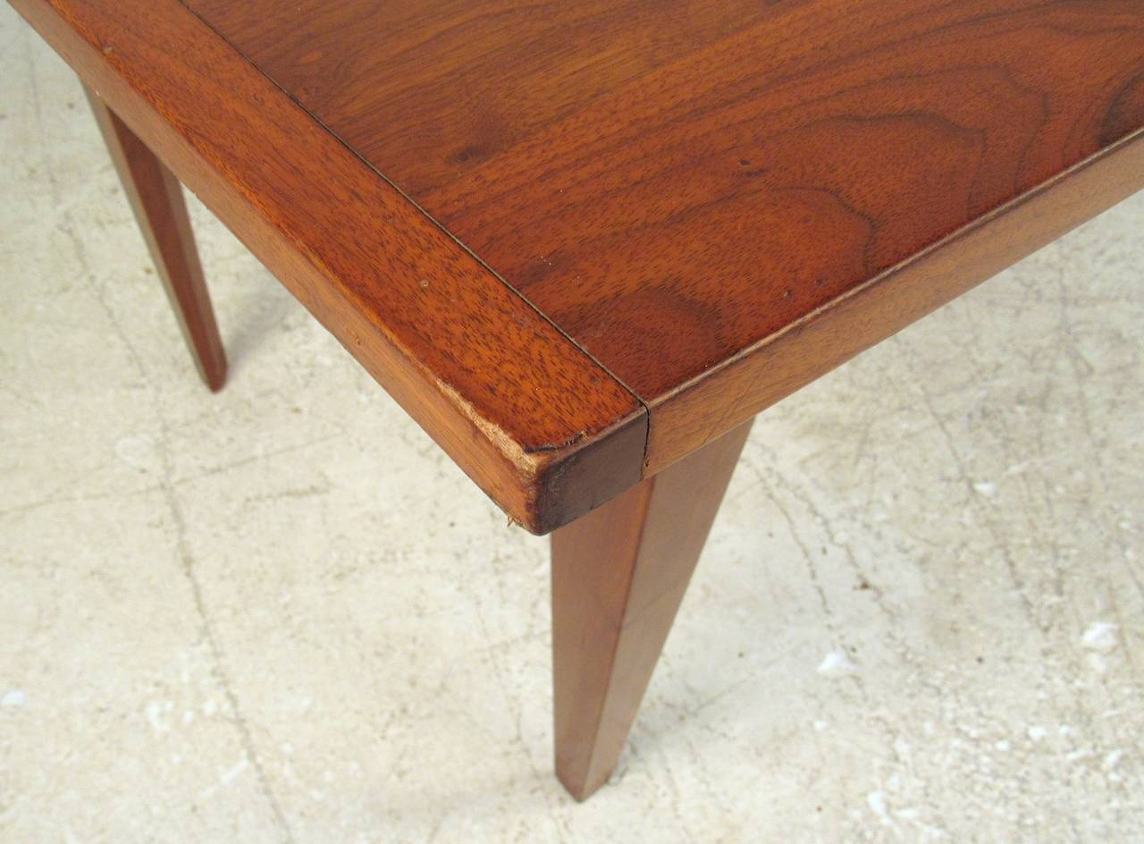 Attractive table with bowed sides that give a subtle hexagon shape. Walnut grain, tapered legs, straight forward stylish design.  (Please confirm item location - NY or NJ - with dealer)