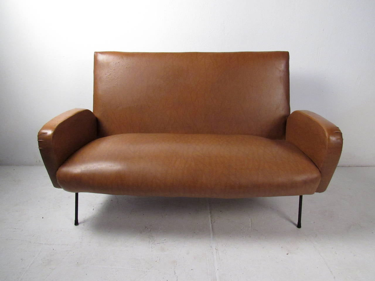 This Mid-Century Italian settee features a sculpted frame with iron legs which offers a modern accent and comfortable seating to any home or office space. Vintage modern two-seat sofa makes the perfect occasional seating for any interior.  Please