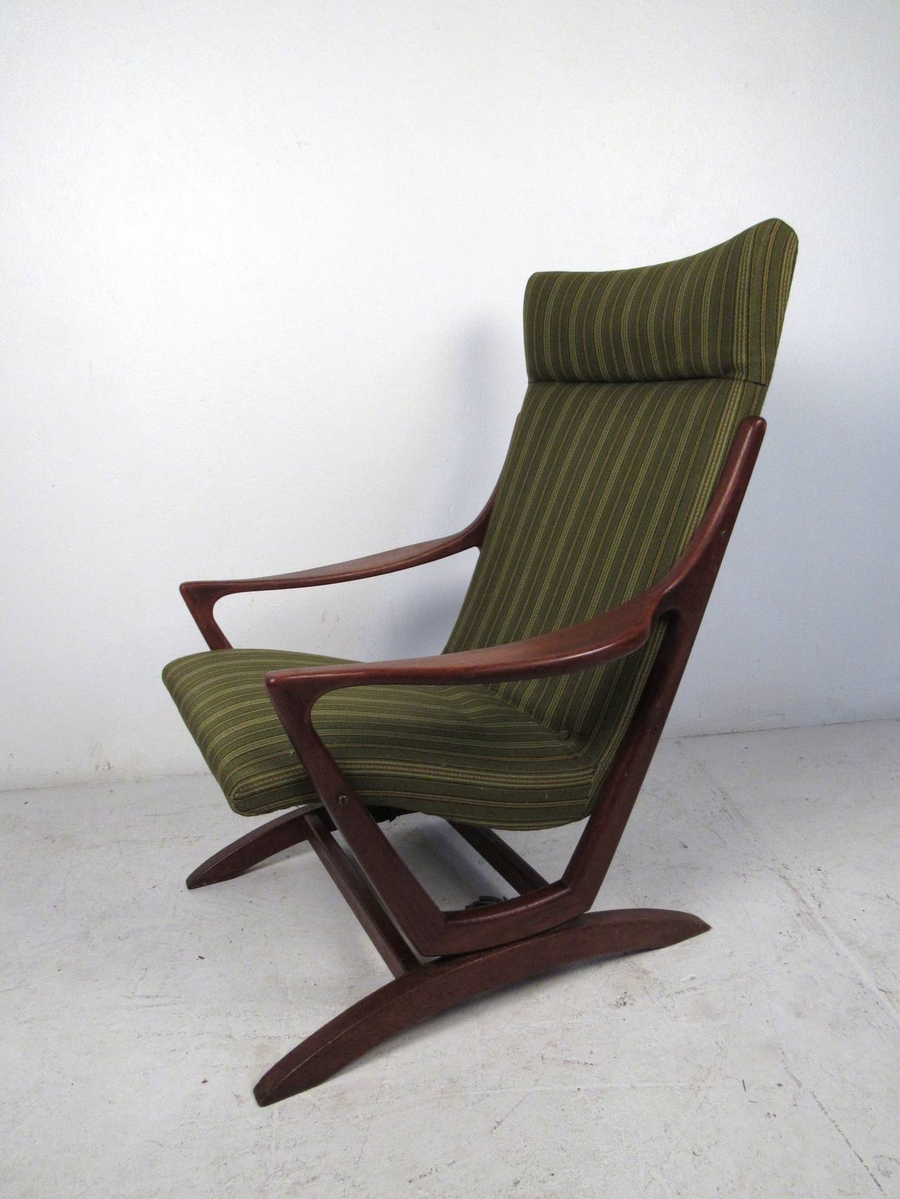 This mid-century modern rocking chair in the style of Adrian Pearsall features a solid walnut construction and vintage upholstery which offers a modern flare and comfortable seating for any home or office space.  Please confirm item location (NY or