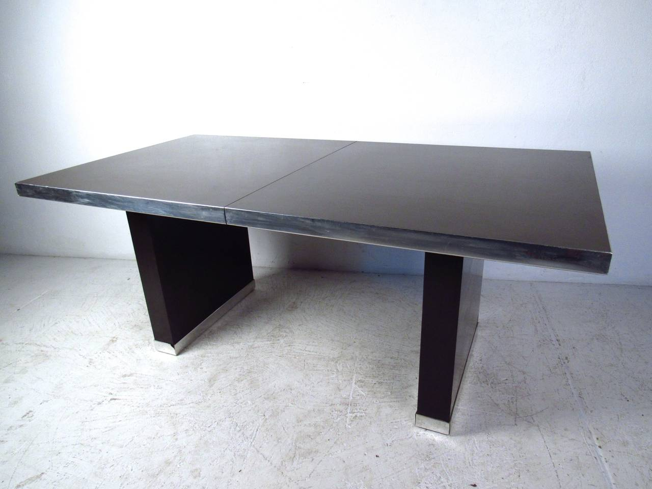 This beautiful dining table was designed by Pierre Cardin and features stylish chrome trim and two leaves for added length (20