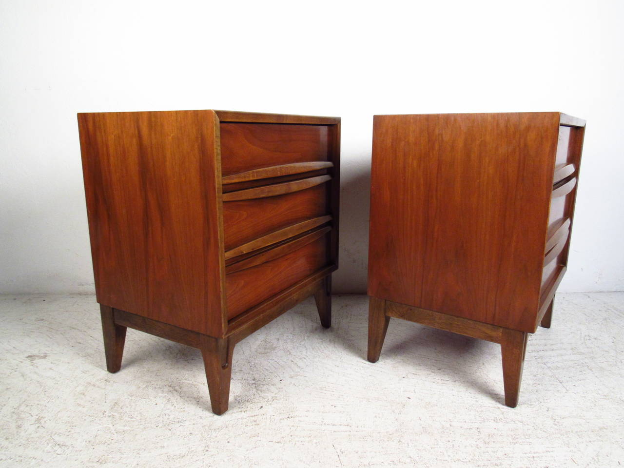 This beautiful pair of vintage nightstands features three drawer design with sculptural pulls and tapered legs. Room for concealed storage and stylish presentation couples with a wonderful walnut finish to make these the perfect addition to any