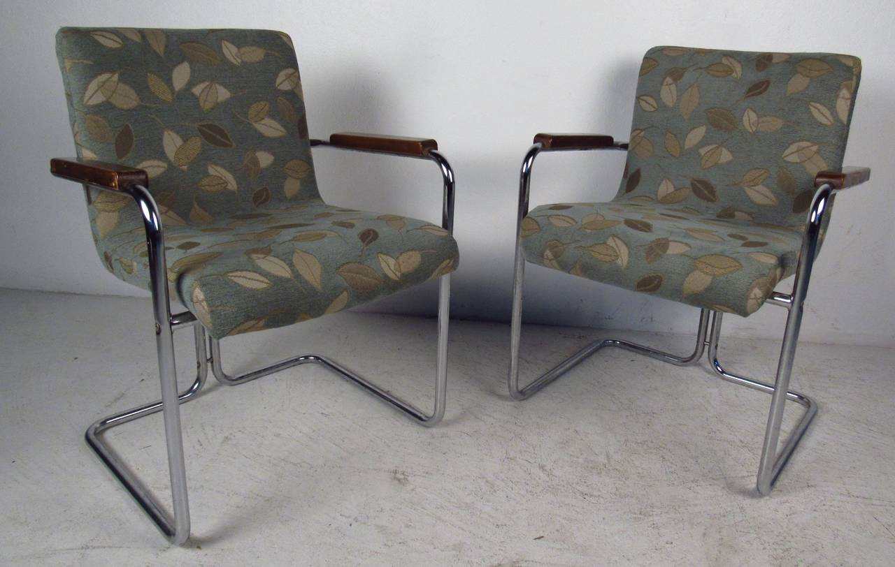 Mid-century modern style dining chairs feature tubular steel and upholstered chairs with wooden armrests. Perfect chairs for kitchen or dining room use. Please confirm item location (NY or NJ) with dealer.