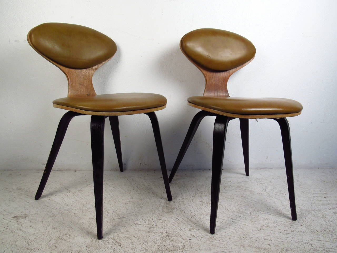This pair of mid century chairs in the style of Norman Cherner feature a bentwood design, original vinyl upholstered seat backs, and black painted tapered legs which offer a modern accent to any home or office space.