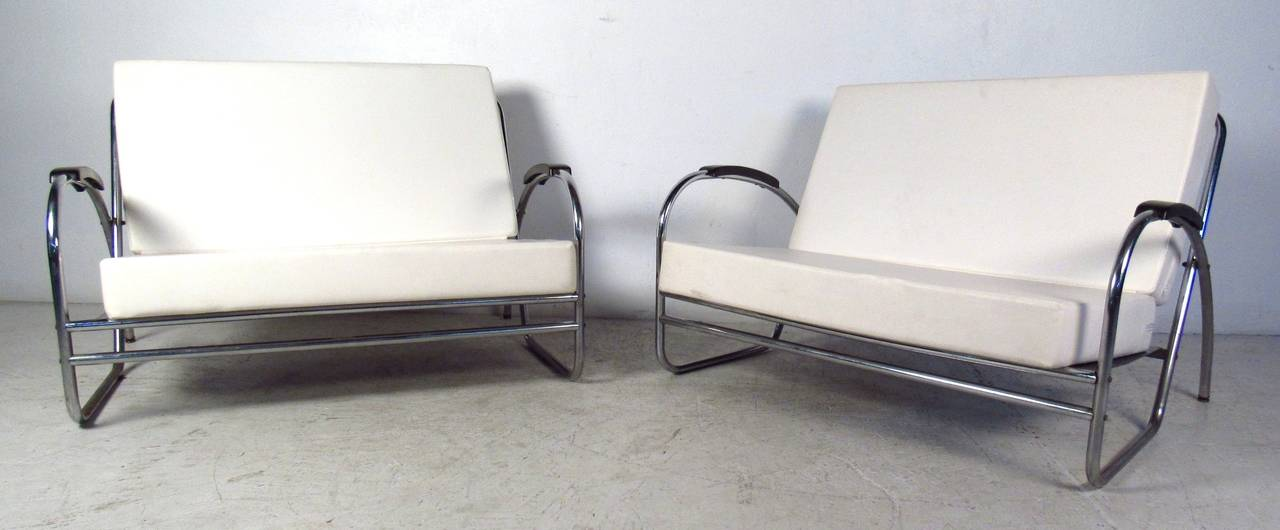 Great pair of tubular chrome love seats by Royal Metal feature quality mid-century modern construction. A sleek design with overstuffed removable cushions covered in white vinyl. The oversized  48