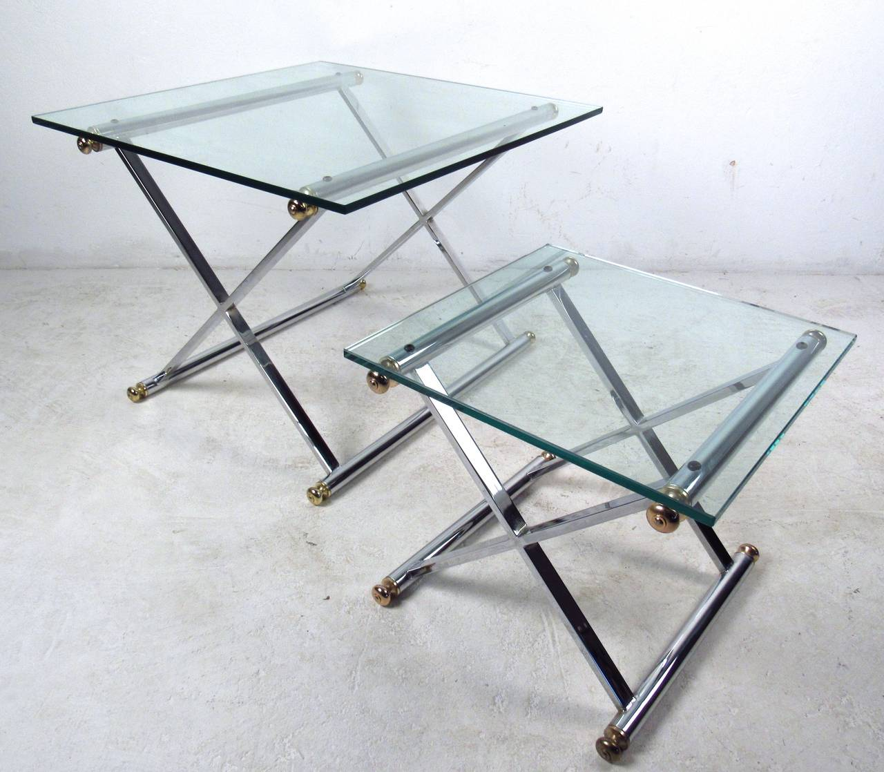 This matching pair of end tables features heavy chrome x-frame bases, unique brass details, and thick glass tops. Stylish addition to any seating area, please confirm item location (NY or NJ). The smaller table measures 17.5w x 17.5d 16h, the larger