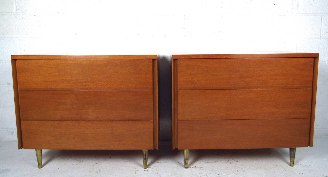 This exquisite pair of matching three-drawer dressers features unique straight lines, plenty of storage space, and tapered brass legs. Unique vintage finish and quality construction make this an excellent addition to any interior. Matching dresser
