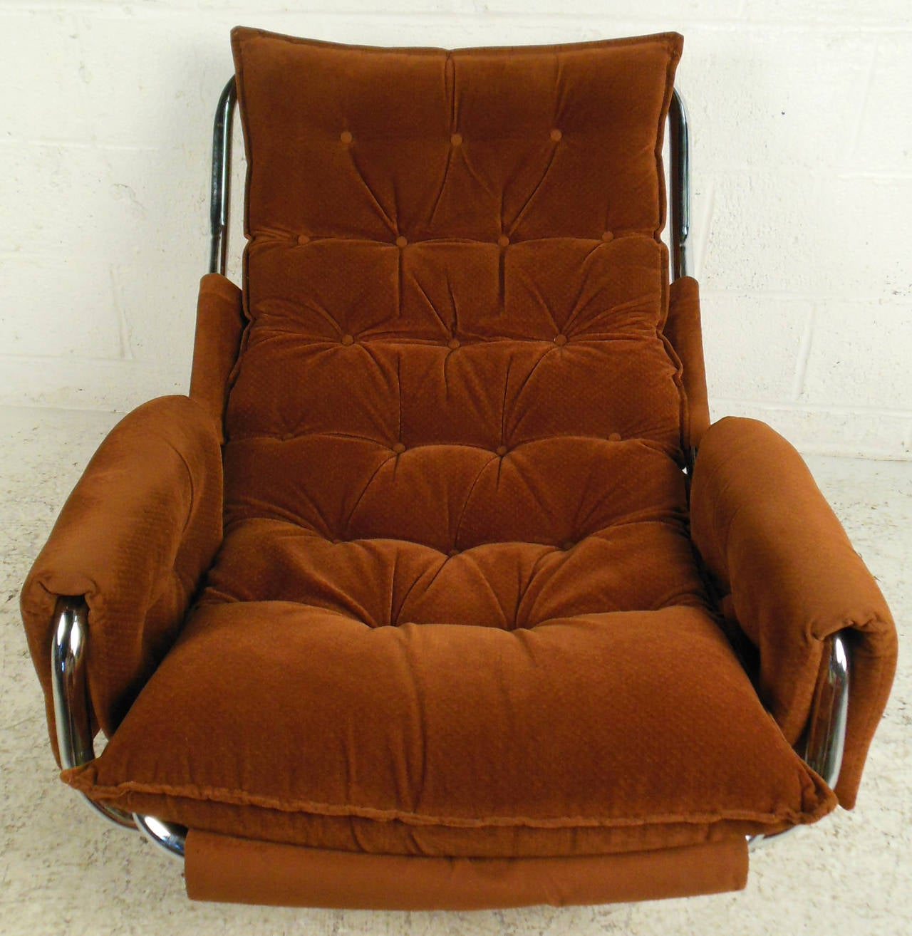 Vintage-modern lounge chair featuring sturdy tubular chrome base, comfortable tufted cushions and adjustable back. The retro style of this mid-century modern sling style chair makes a stylish addition to home or business seating arrangement.