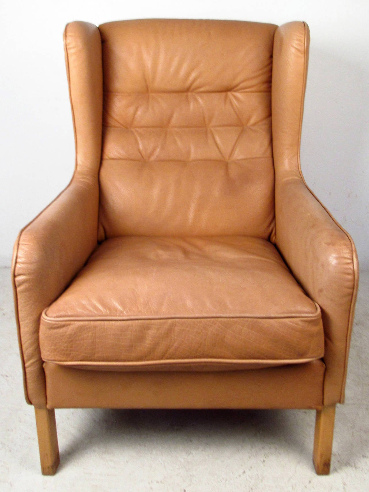Vintage-modern leather lounge chair, featuring tufted wing back, blonde legs and removable seat cushion. Designed in the manner of Børge Mogensen.  Please confirm item location NY or NJ with dealer.
