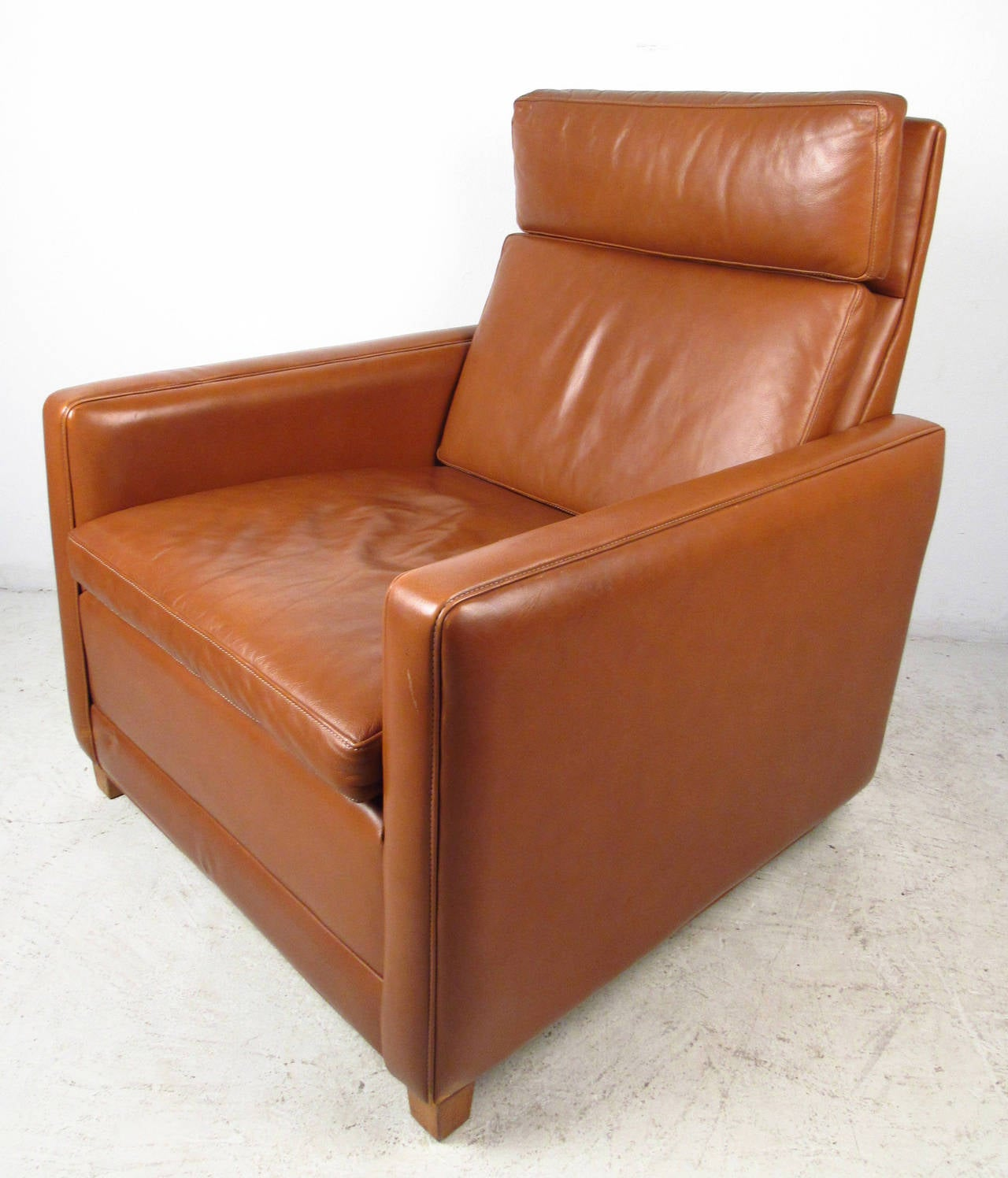Vintage modern leather lounge chair features a unique design with blonde wood feet in the front and chrome wheels in the back, designed by Børge Mogensen. This unique shape with it's ergonomic seat back makes a comfortable chair for home or business