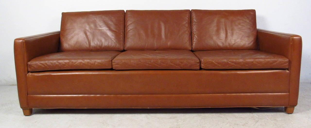 Vintage-modern sofa features brown leather upholstery, unique blonde feet in front and chrome wheels in back, designed in the style of Børge Mogensen.  Please confirm item location NY or NJ with dealer.