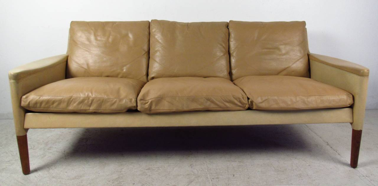 This stylish vintage three-seat sofa features vintage leather upholstery with Scandinavian style flared arms. Unique Danish modern design this stylish couch comfortably seats 3. Striking mid-century addition to home or business seating. Please