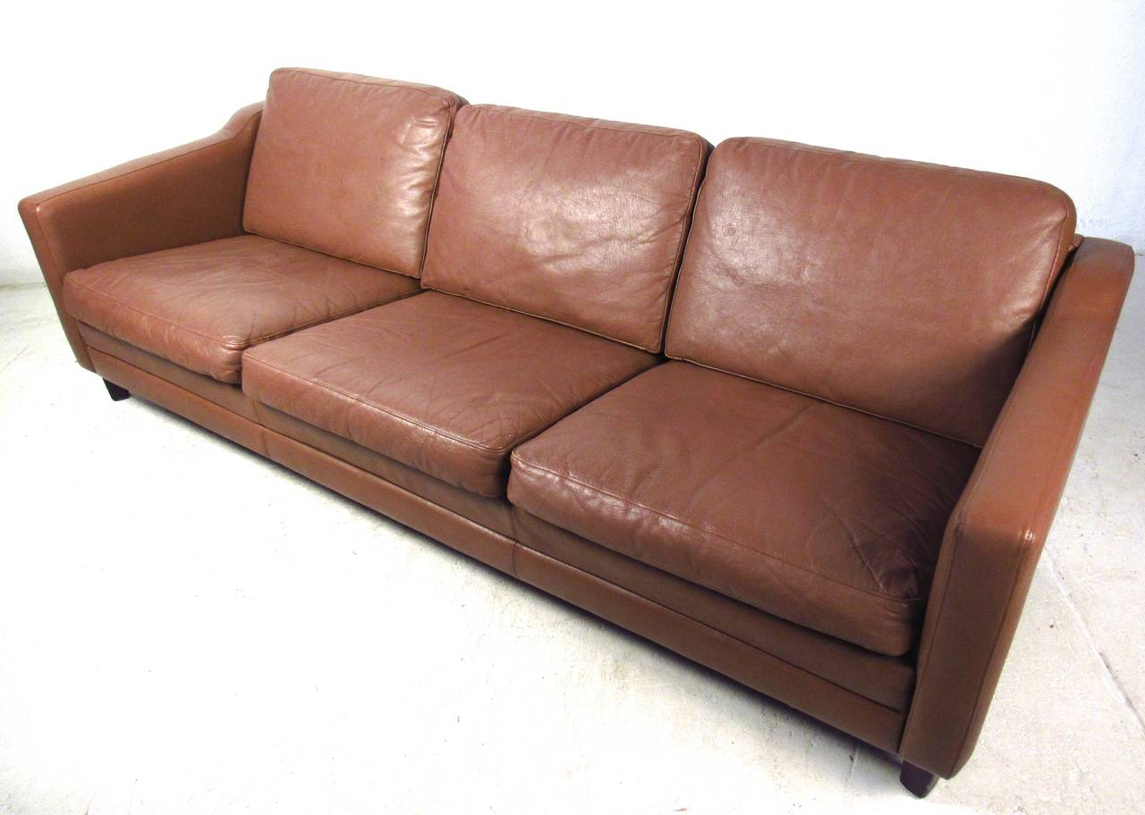 This beautiful Mid-Century Modern sofa makes a comfortable and stylish addition to any seating arrangement. Quality vintage leather, low profile legs, and uniquely sculpted armrests add to the charm of the piece. The Scandinavian Modern style is