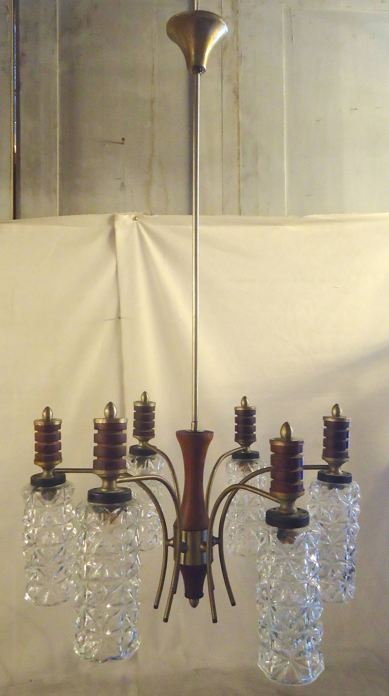 Mid-century modern six arm chandelier with great cut glass shades. Brass arms and wood accents with a long stem to the ceiling.  (Please confirm item location - NY or NJ - with dealer)