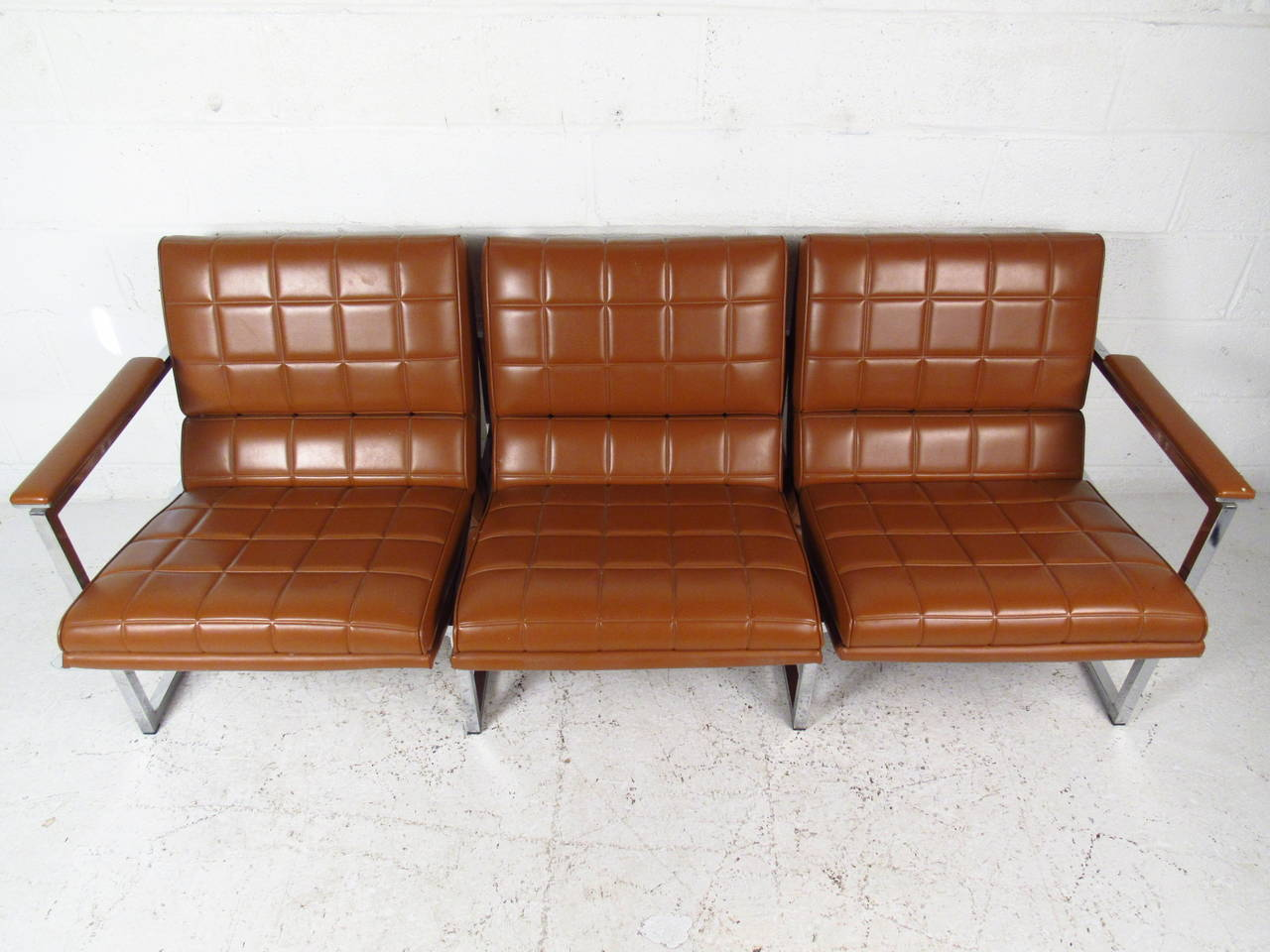 This beautiful vintage three-seat sofa features uniquely designed vinyl upholstery on a sturdy chrome frame. Padded armrests and waterfall style seat backs add to the charm of the piece, which makes a fantastic mid-century addition to any seating
