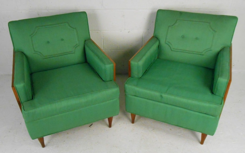 Comfortable pair of Mid-Century upholstered lounge chairs with walnut trim. These attractive chairs boast a plush green fabric with embossed designs, thick padded seats, and tapered legs. The two-tone design with square sides and a tufted back rest