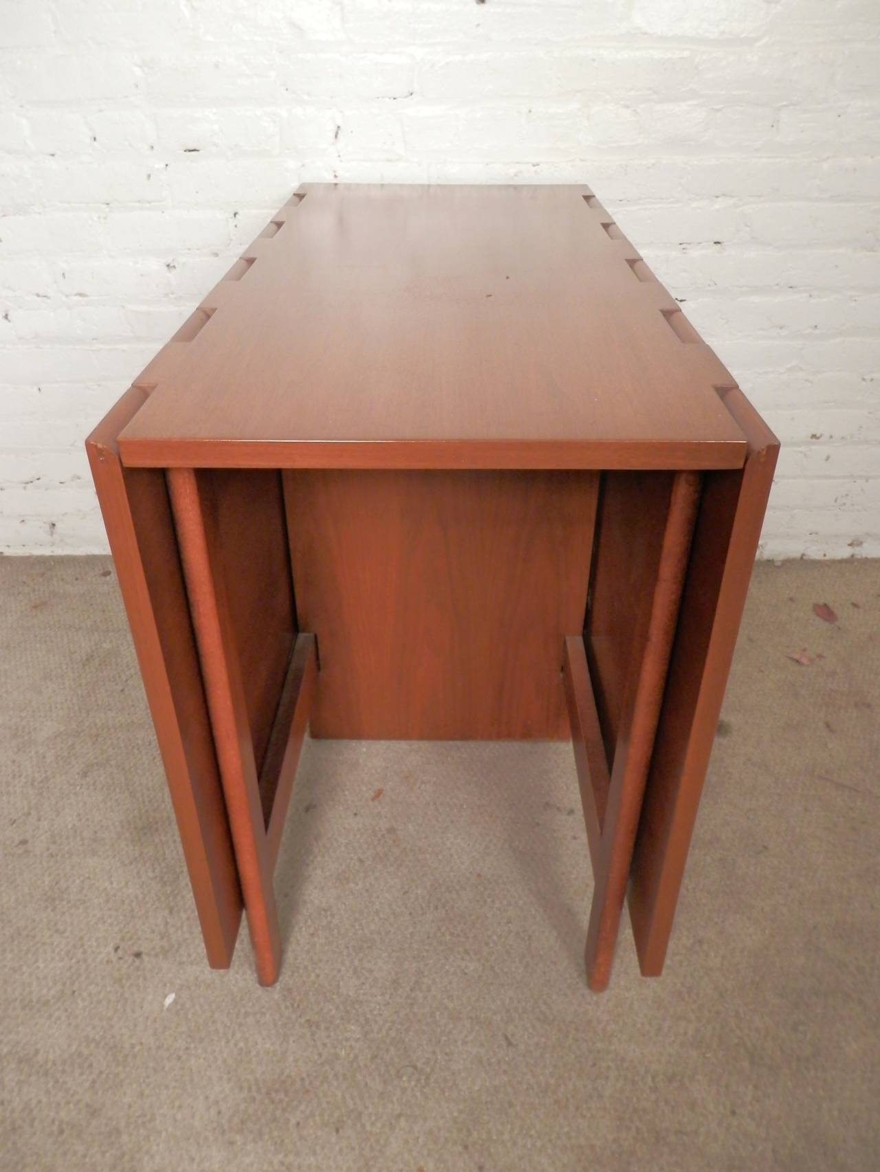 """Vintage modern dining table for Herman Miller featuring the unusual wooden hinged top. Works well in small spaces, and can be adjusted to seat 2 to 6 people or used as a desk or console table. Measures 18-65"""" wide.  (Please confirm item"""