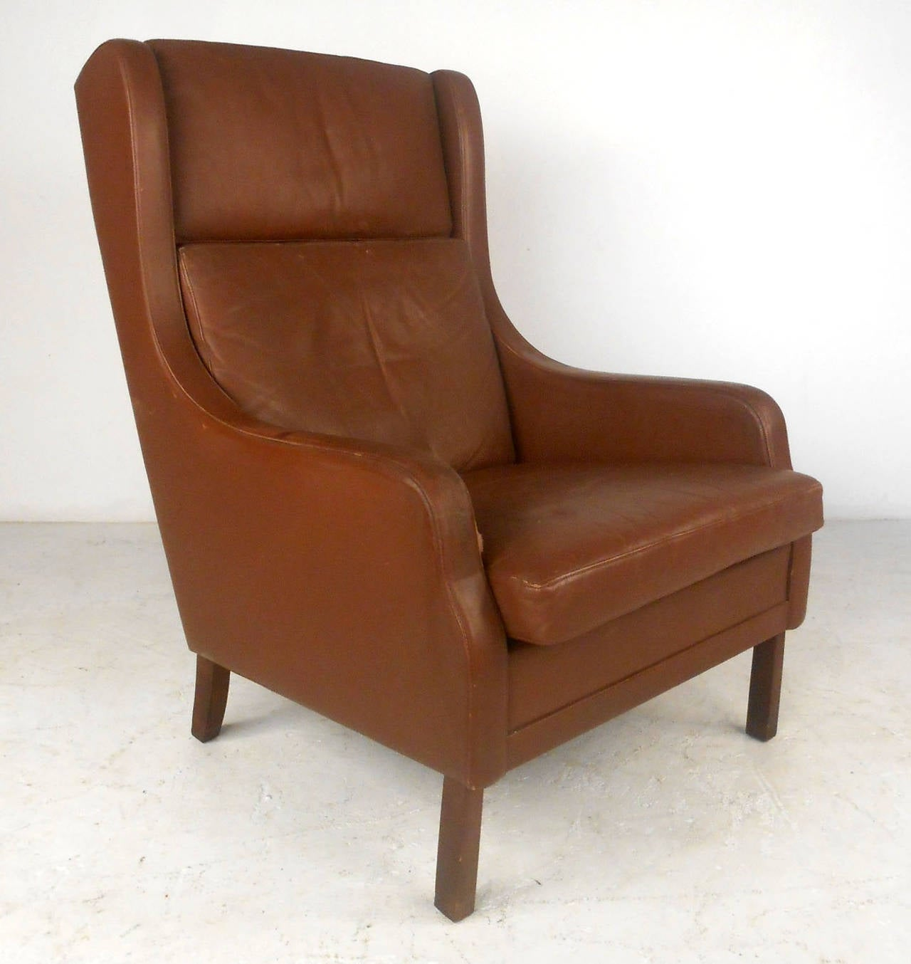 This wonderful vintage leather chair features a remarkably comfortable three-piece cushion system, Classic Mid-Century shape, and rich vintage worn leather. Please confirm item location (NY or NJ).
