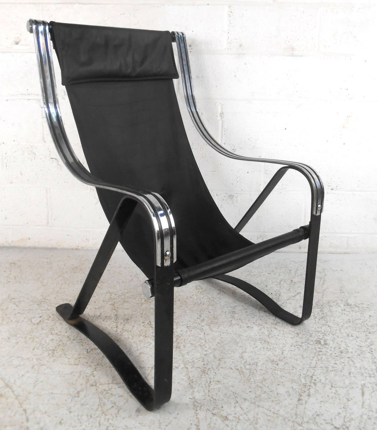 This stylish chair combines leather, iron, and chrome to create a comfortable midcentury seating option for any room. Unique head rest, decorative chrome, and cantilevered base make this a wonderful addition to any room. Please confirm item location