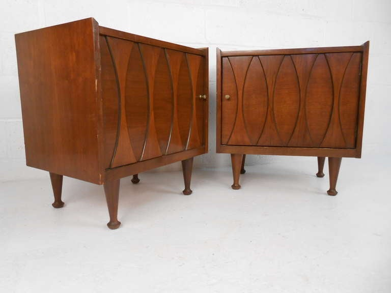Stylish pair of midcentury American walnut nightstands by Hoke Wood Products make a unique addition to any interior as nightstands or end table. Spacious storage cabinets, unique drumstick legs, and sculpted decorative fronts add to the appeal of