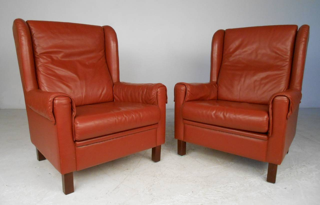 This stylish pair of Scandinavian Modern lounge chairs features vintage reddish leather upholstery, spacious and comfortable seats, and sculpted wingback design. Perfect pair of mid-century club chairs for any interior. Please confirm item location