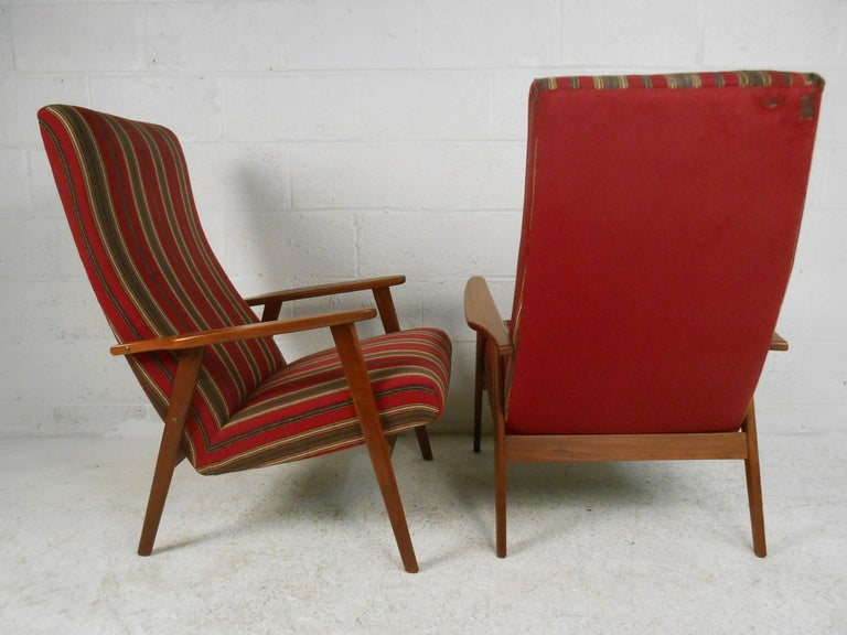This stylish pair of Danish teak high back upholstered lounge chairs feature unique vintage fabric and elegant Scandinavian design. Great Mid-Century Modern seating for any setting. (Please confirm item location NY or NJ with dealer).