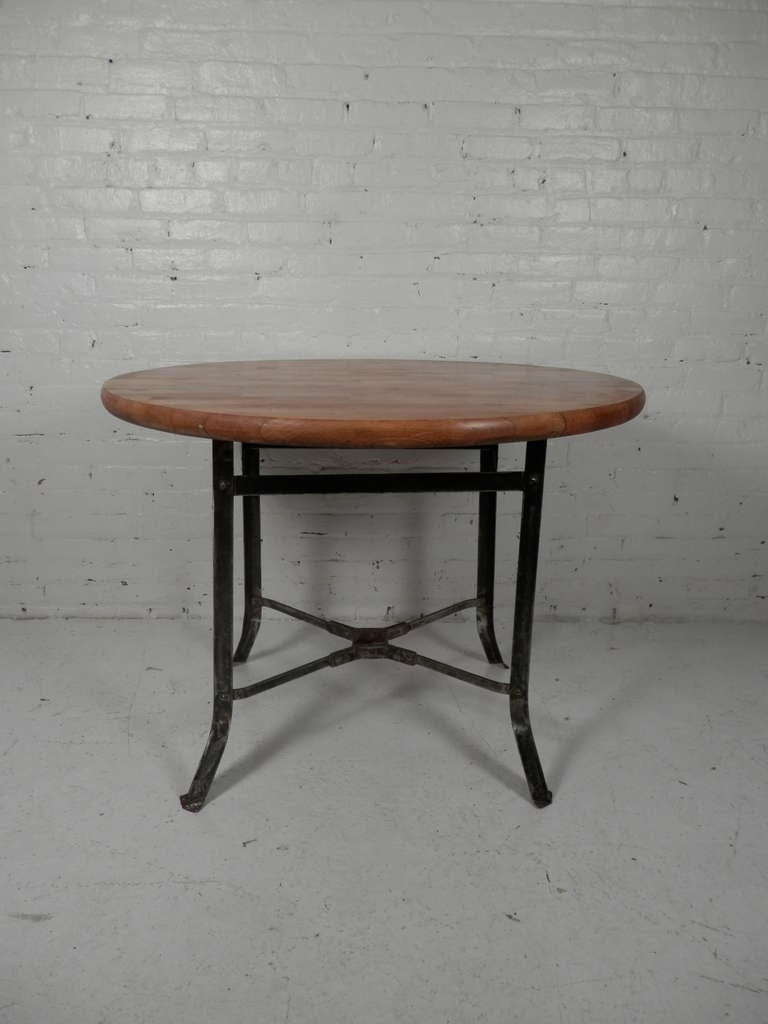 butcher block dining table with industrial metal base at