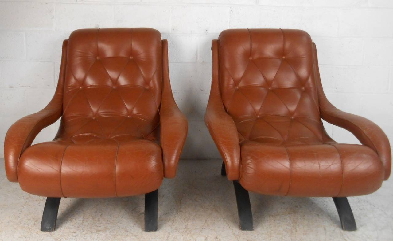 This beautiful pair of chairs combines tufted leather, unique curved legs and padded ergonomic armrests to create a luxurious lounge chair for any seating arrangement. Please confirm item location (NY or NJ).