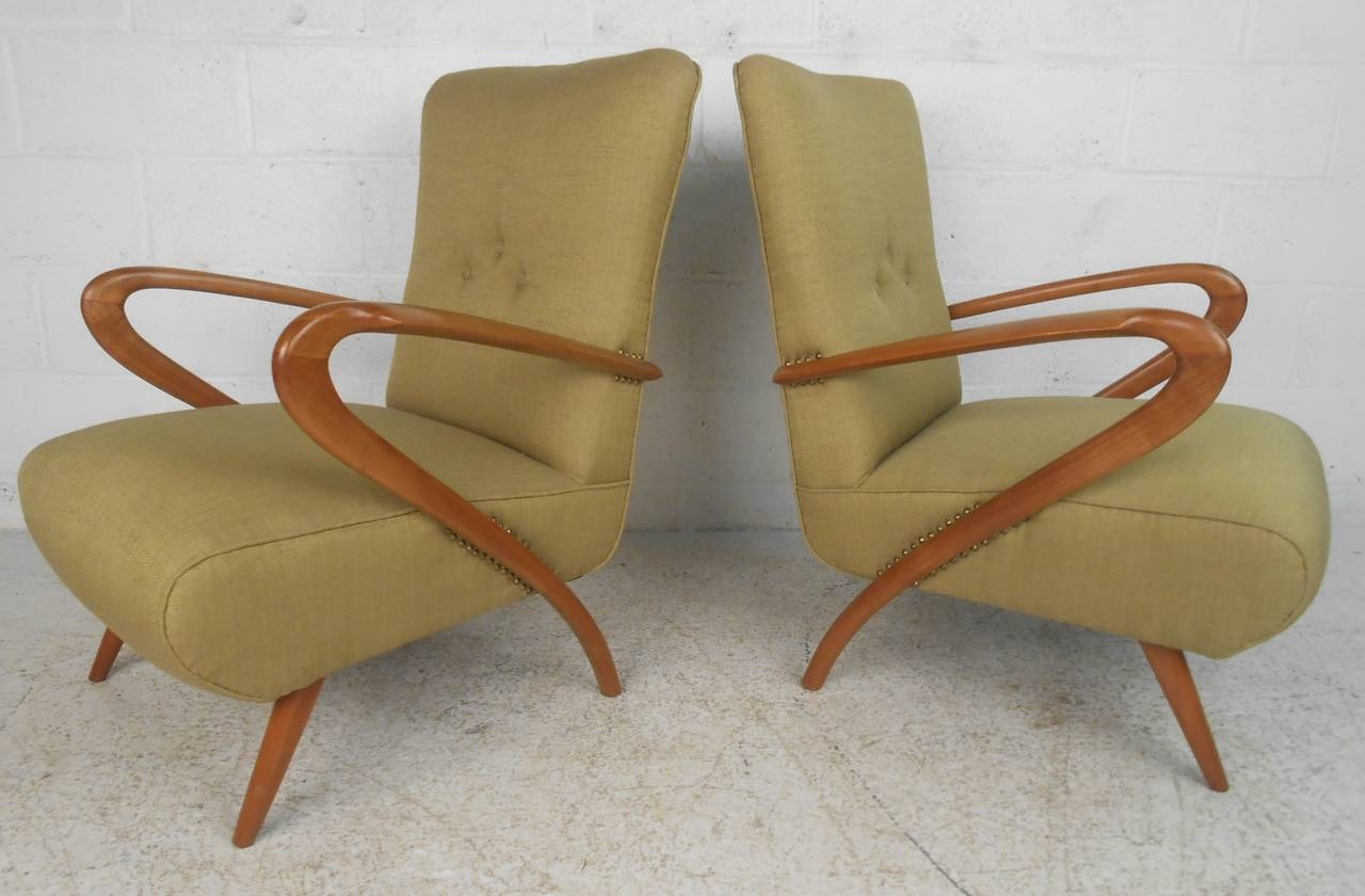 Stylish Italian modern armchairs in the style of Paolo Buffa make an elegant and comfortable addition to any seating arrangement. Comfortable proportions and sculptural carved wood frames. Please confirm item location (NY or NJ) with dealer.