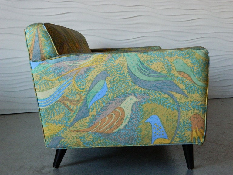 This American mid century modern sofa in the style of Paul McCobb features clean, simple lines, colorful bird-motif upholstery, and tapered legs.