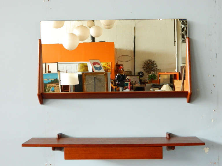 This handsome teak two-piece mirror and floating shelf is attributed to Aksel Kjersgaard. Made in the 1960s. The floating shelf has a single drawer.