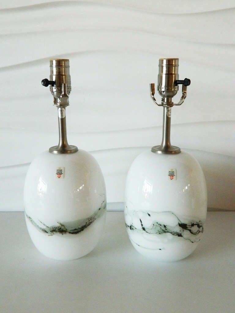 This stunning pair of glass lamps was designed by Michael Bang for the Danish company Holmegaard. These lamps were part of the Symmetrisk line.   A pair of white shades measuring 10