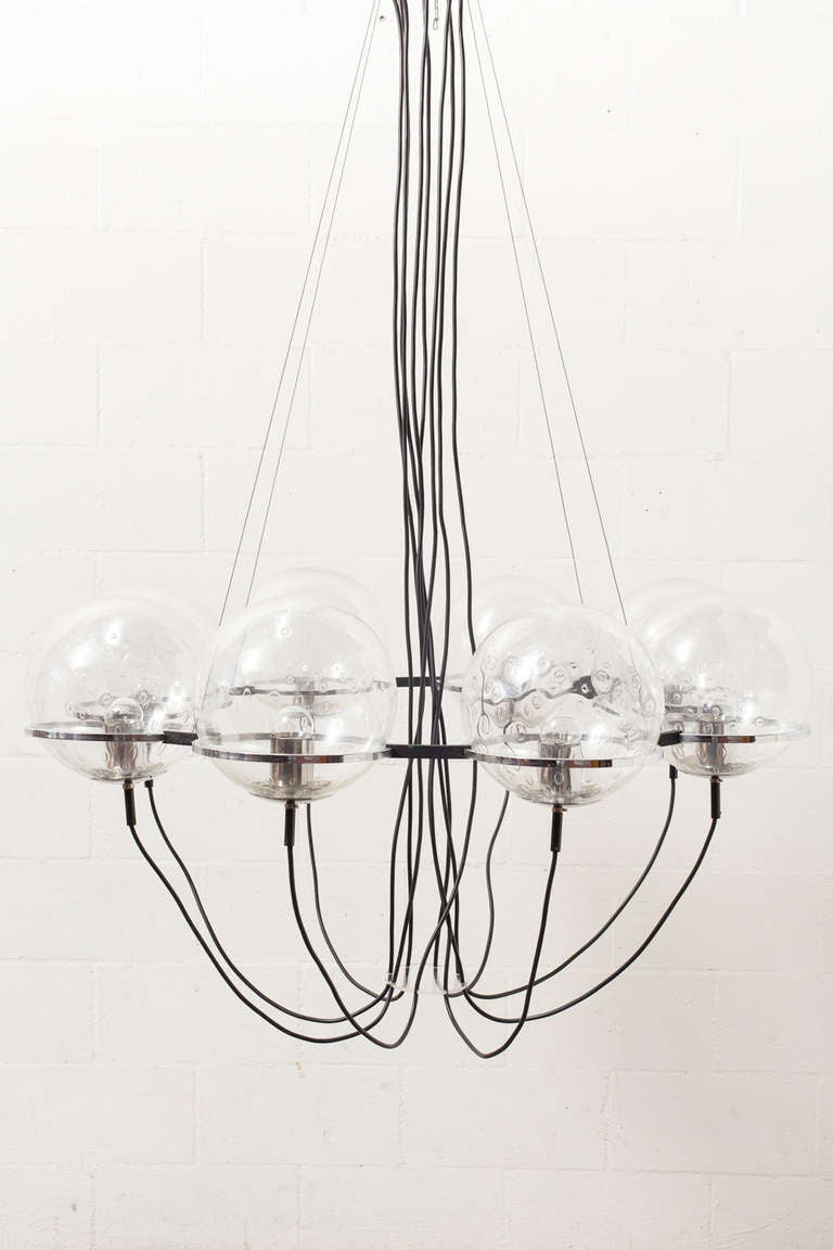 Hanging Steel Ring with Eight Handblown Glass Bulbs. Fixtures for the Bulbs in Chrome plated Steel. Nearly 4' in Diameter. The Chandelier is Mounted to the Ceiling with Four Steel Cables. Rewired for USA.