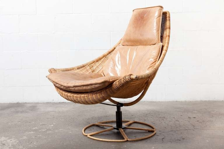 Wicker Lounge Chair with Leather Upholstered Cushion on a Wicker Wrapped Swiveling base. An unimaginable Combination of Materials for an amazing chair.