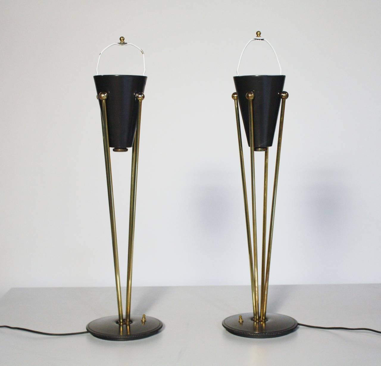 Pair of Stiffel lamps by Gerald Thursten. Brass tripod design with restored linen drum shades and diffused plexiglass filters. Base has a convenient power switch.