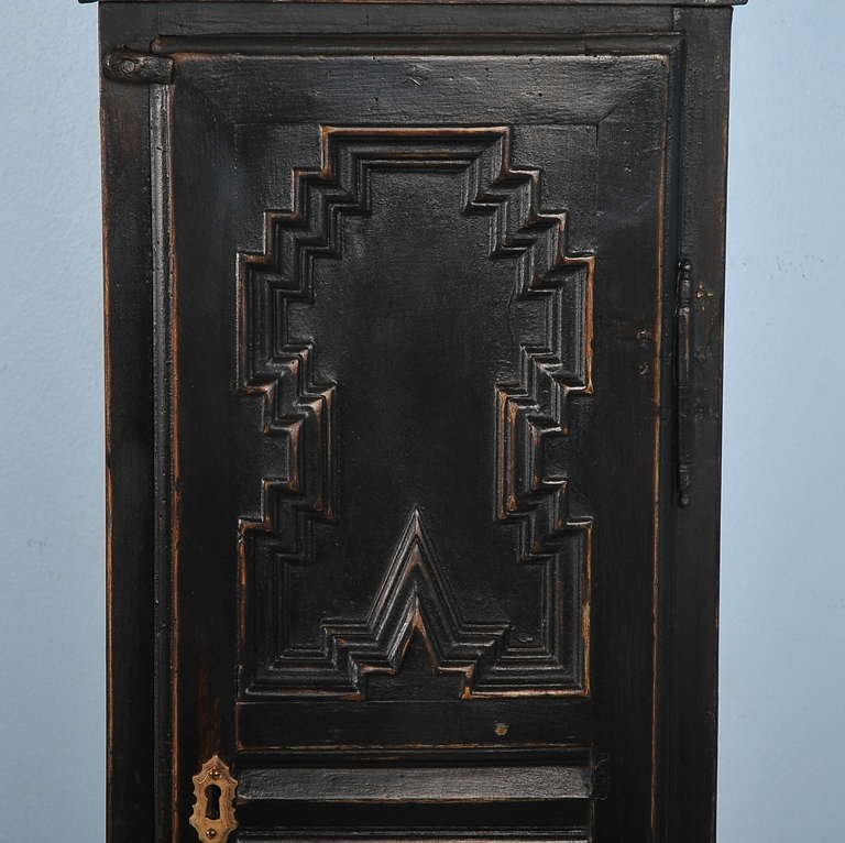 Intriguing geometric carved panels accentuates the strong lines of this black painted grandfather clock from Denmark. Note the ornate face with etched brass and filigree work. Above the face is a monogrammed centerpiece as well. When this clock was