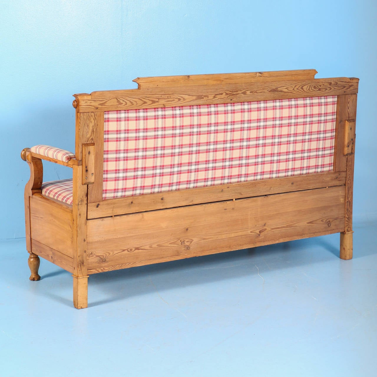 The lovely, simple lines of this bench are true to its Swedish country styling. The gently curved arms, turned feet and dentil molding along the back rest are some of the style elements that combine for a charming affect. The pine is waxed, bringing