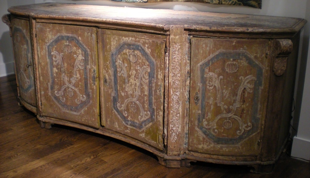 Incredible 17th century painted (original paint) Italian credenza with marbleized drawers concealed behind the four doors of the serpentine shaped facade. Hardware is original.