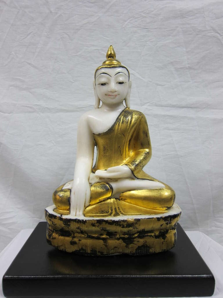 Burmese Alabaster Buddha 19th-20th century, Mandalay Period. Extremely well captured and polished features, exceptional piece. Gold leaf with black lacquer over Alabaster. 17 inches tall without stand, on black stand 19 inches. Wooden black stand