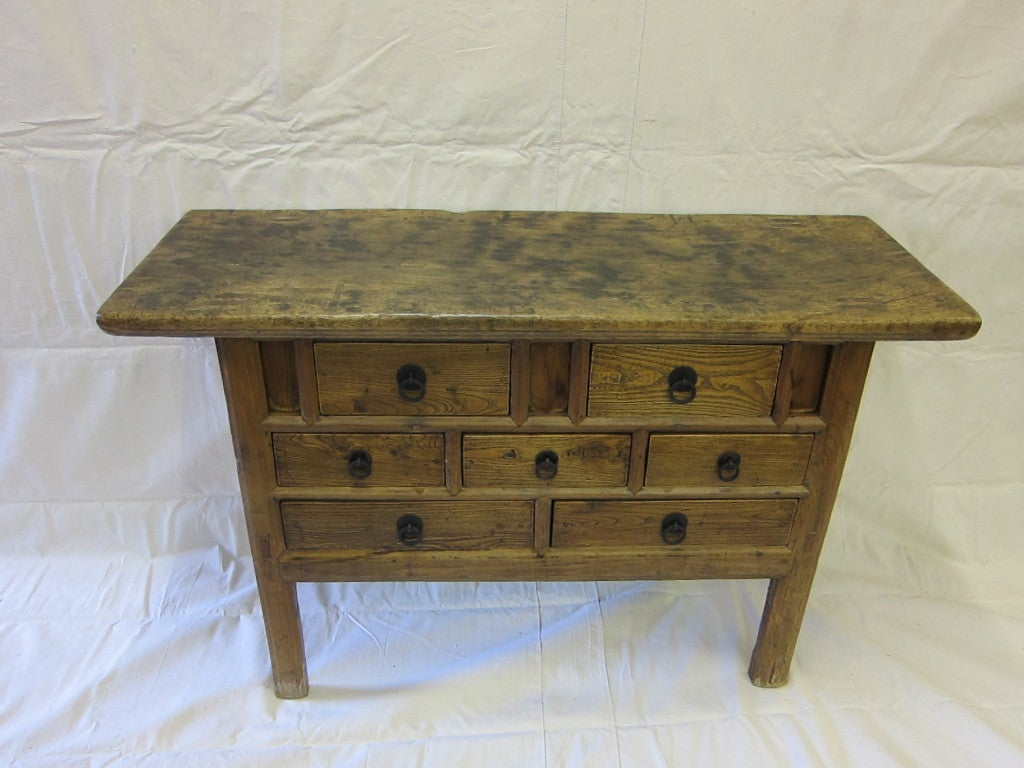19th century Elm wood Chest of Drawers.  Elm wood Console Table having solid one piece top over seven apothecary style drawers with iron ring pulls hardware.  A unique arrangement of drawer design and positioning. A wonderful time endured patina.