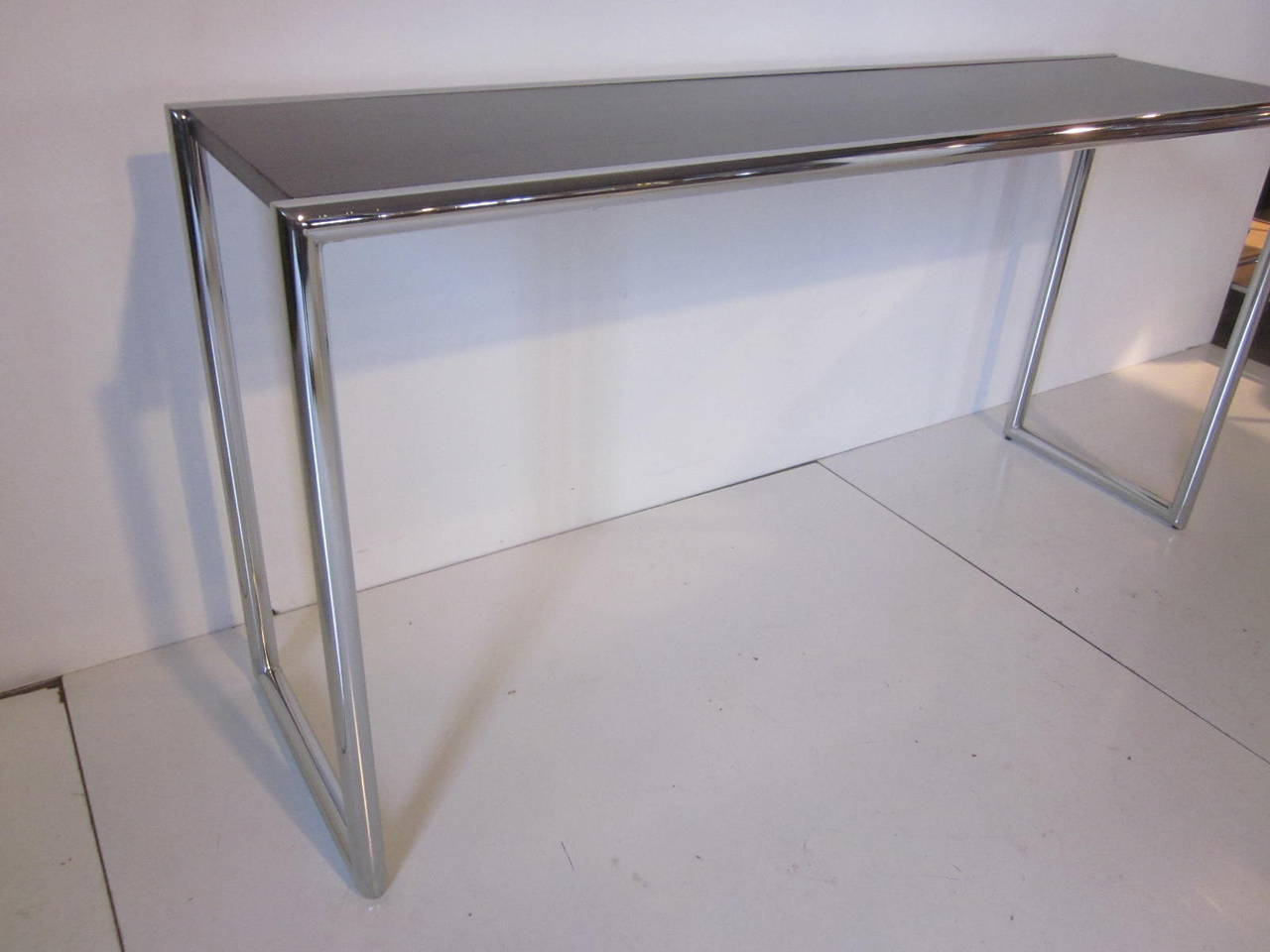 A chrome tubed console table with a dark ebony toned wood top, a clean and tailored design form from the 1970s in the manner of Milo Baughman.